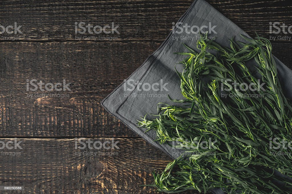Tarragon on the grey napkin on  wooden table top view stock photo