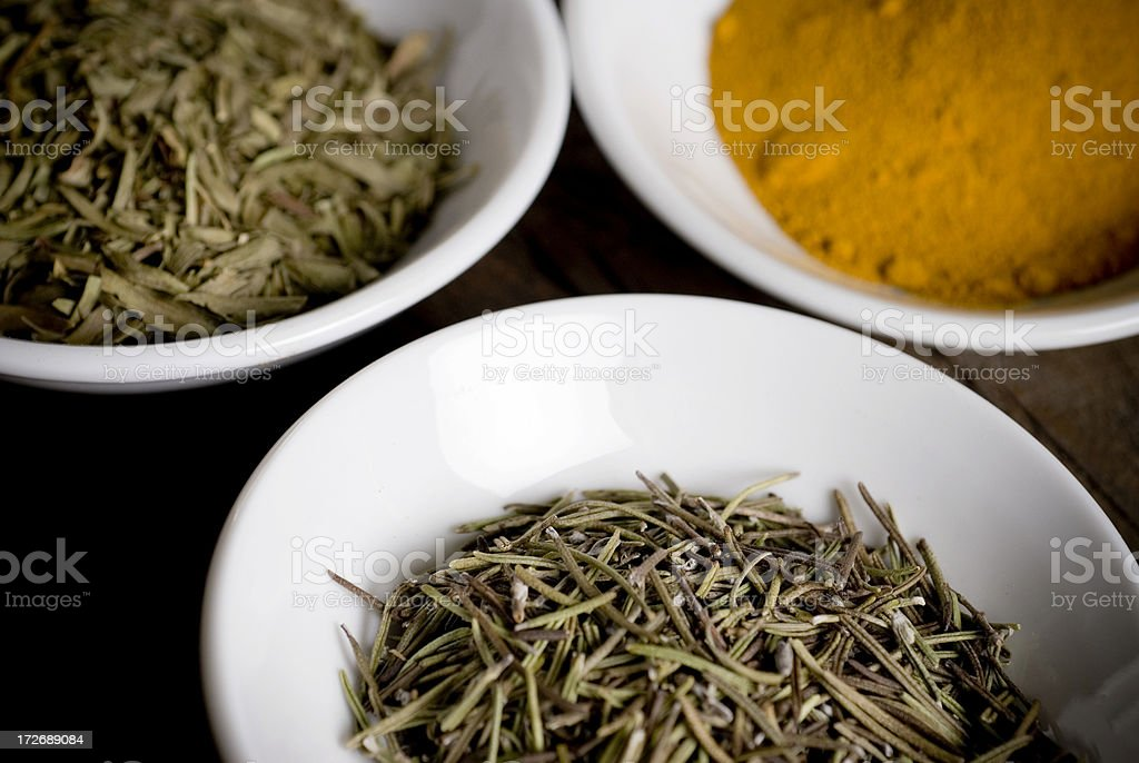 Tarragon, rosemary and turmeric dried spices in white bowls royalty-free stock photo