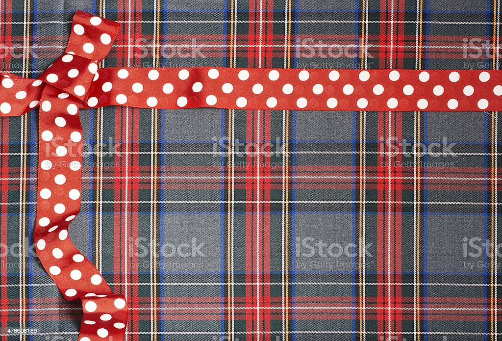 Tartan background texture with polka dots and red ribbon stock photo
