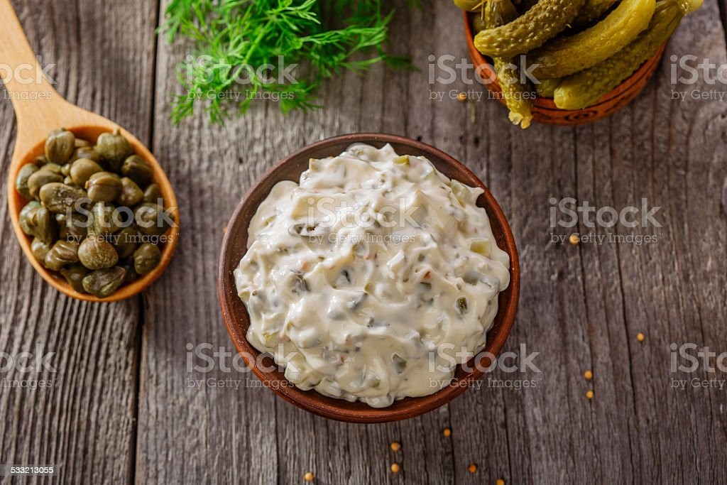 tartar sauce in a gravy boat on a wooden surface stock photo