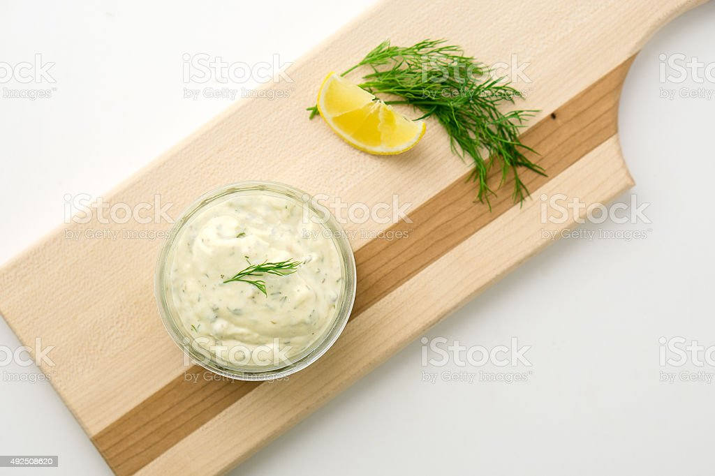 Tartar sauce on a wooden serving board top view stock photo