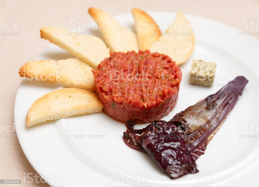 Tartare with toasts and chicory cooked in wine stock photo