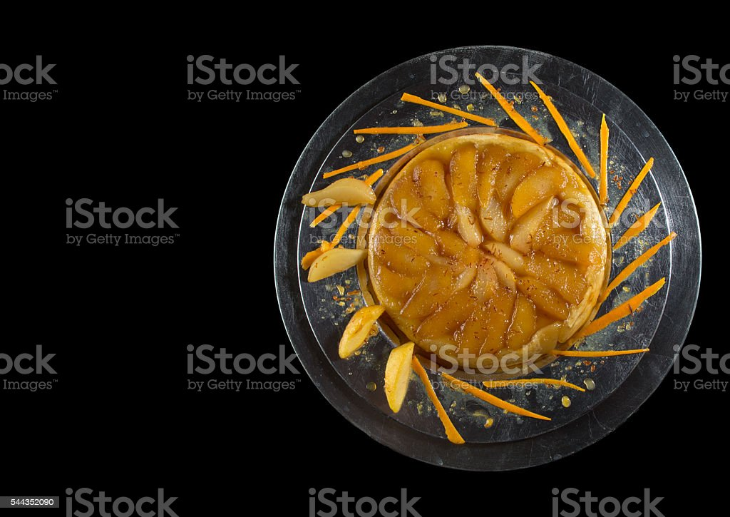 Tarte Tatin on silver plate isolated on black background stock photo