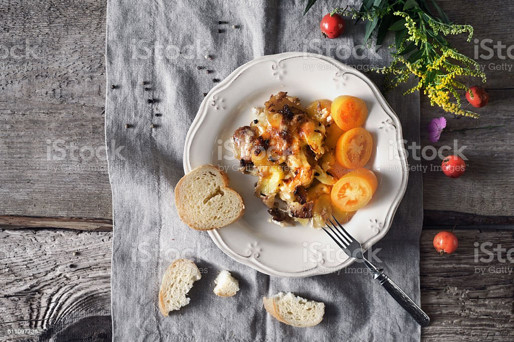 Tartiflette with tomatoes and bread on white plate top view stock photo