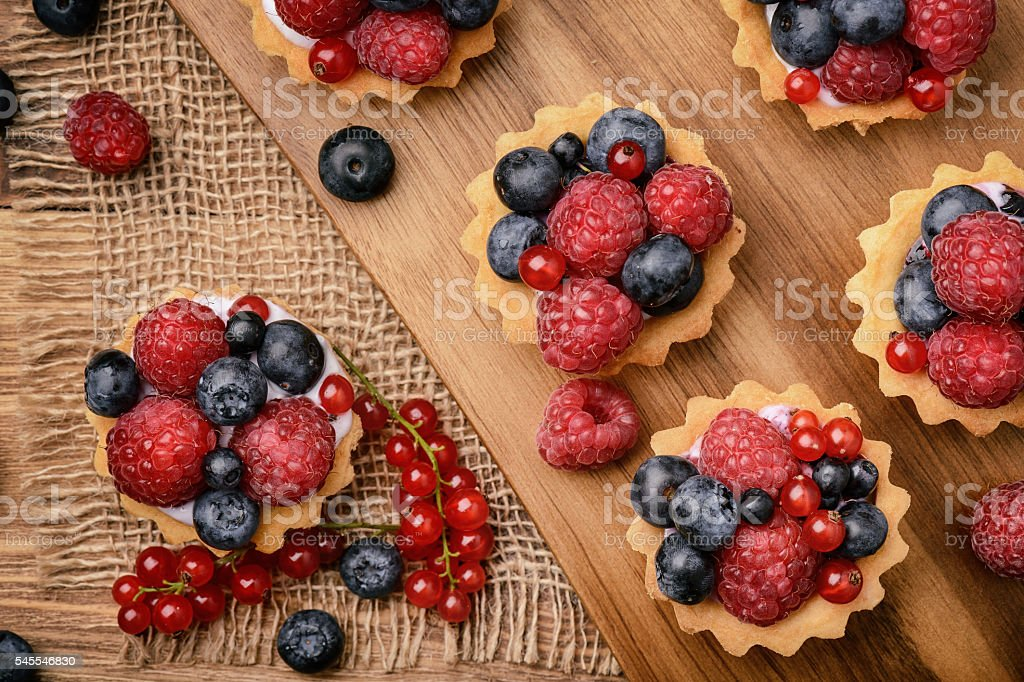 Tartlets with cream, blueberries, raspberries and red currants. stock photo