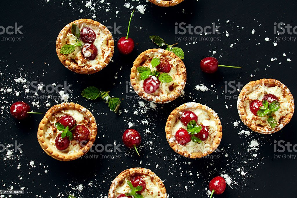 Tartlets with whipped cream and cherry. stock photo