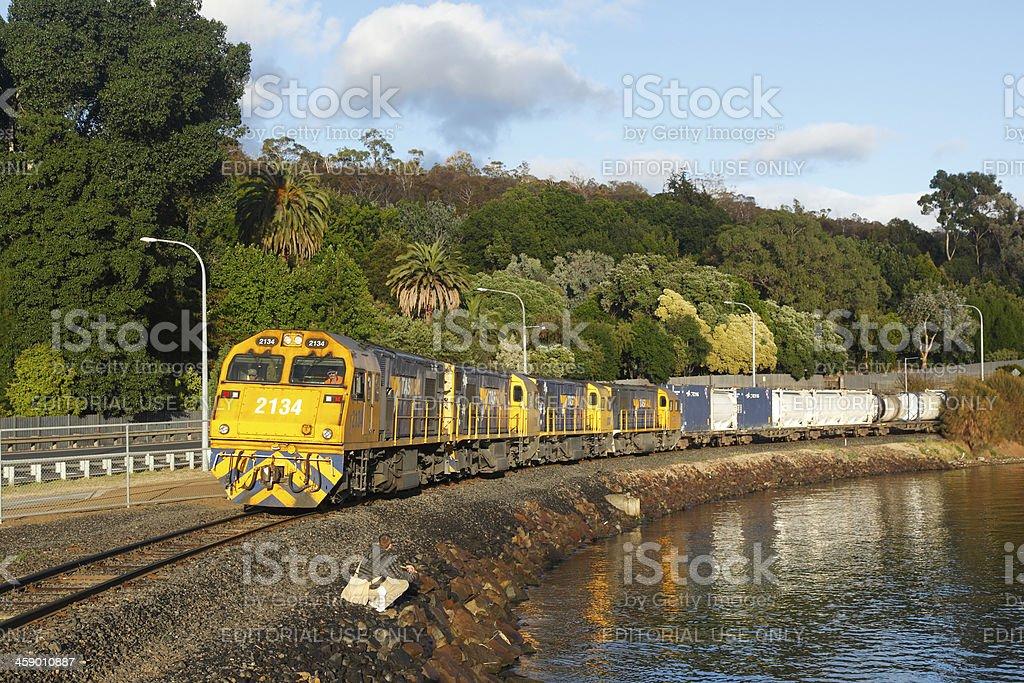 Tasrail train passing fisherman on Derwent shore royalty-free stock photo