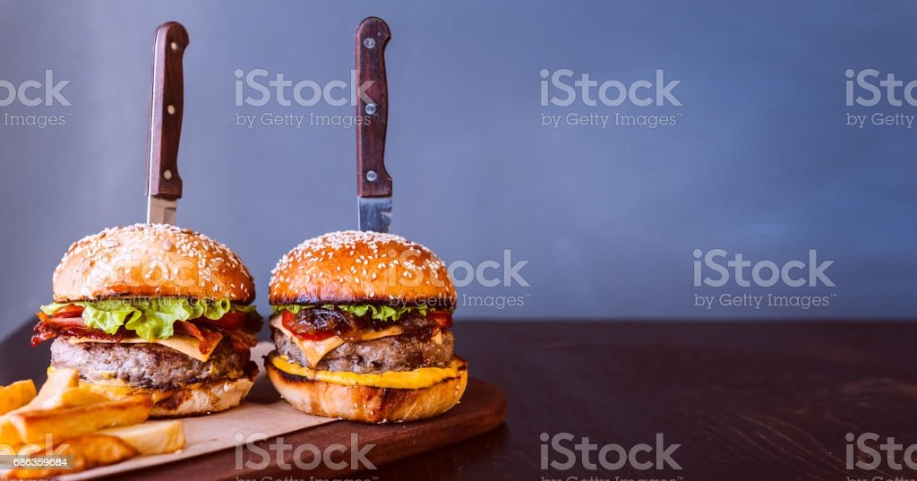 tasty and delicious juicy burger with beef and bacon on a grill. dark wooden background stock photo