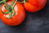 Tasty and fresh tomatoes on a black stone serving board
