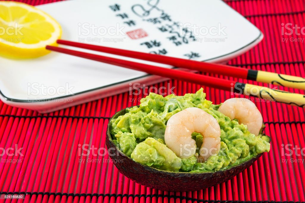 Tasty avocado salad with two shrimps, lemon and red chopsticks stock photo