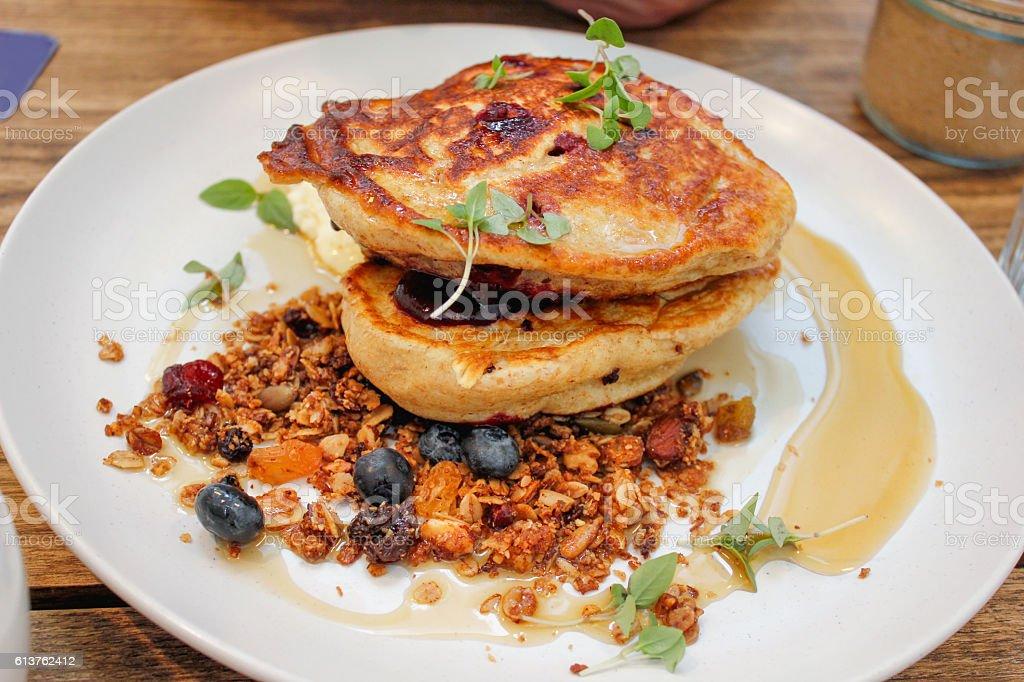 Tasty blueberry pancake with granola and honey stock photo