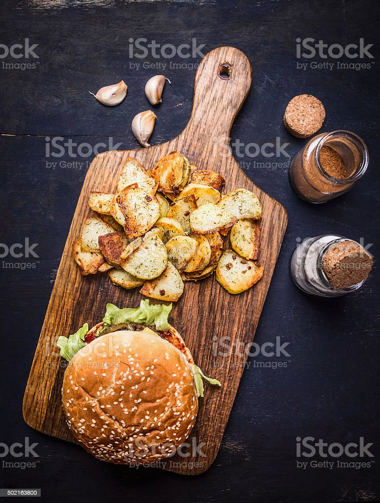tasty burger cutting board potato wedges wooden rustic background top stock photo