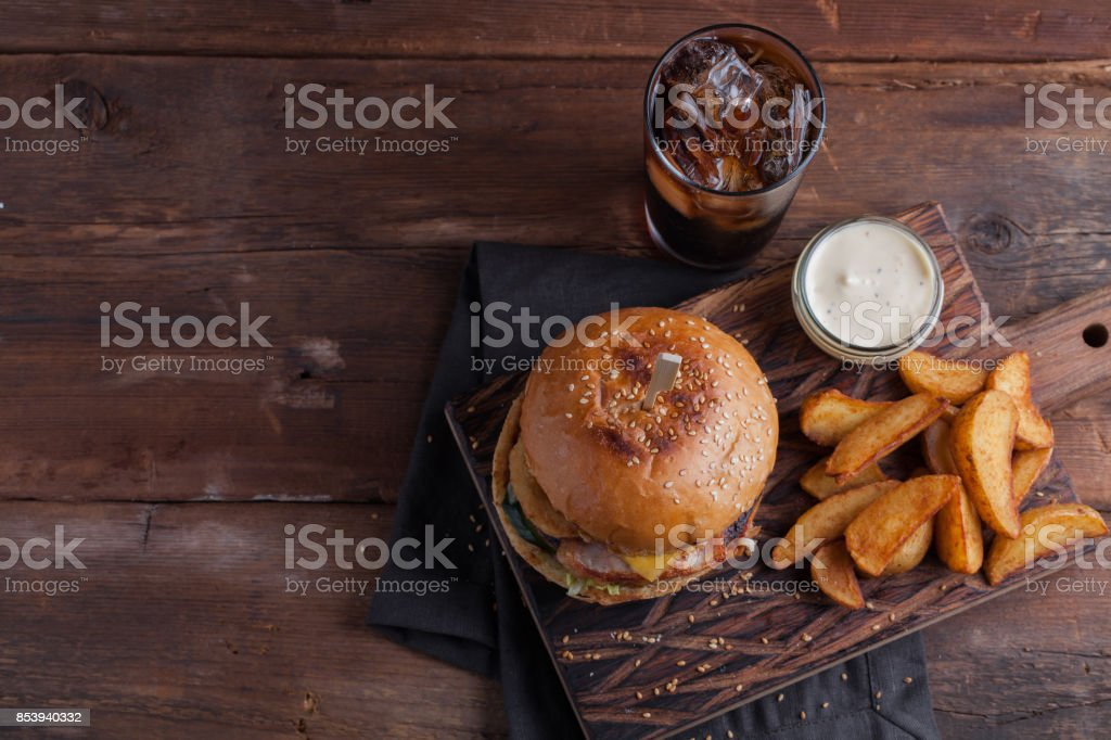 A tasty Burger with snacks in the form of potatoes with white garlic sauce and a glass of cold Cola. juicy Burger with onion rings, bacon and cheese on a dark wood background. stock photo