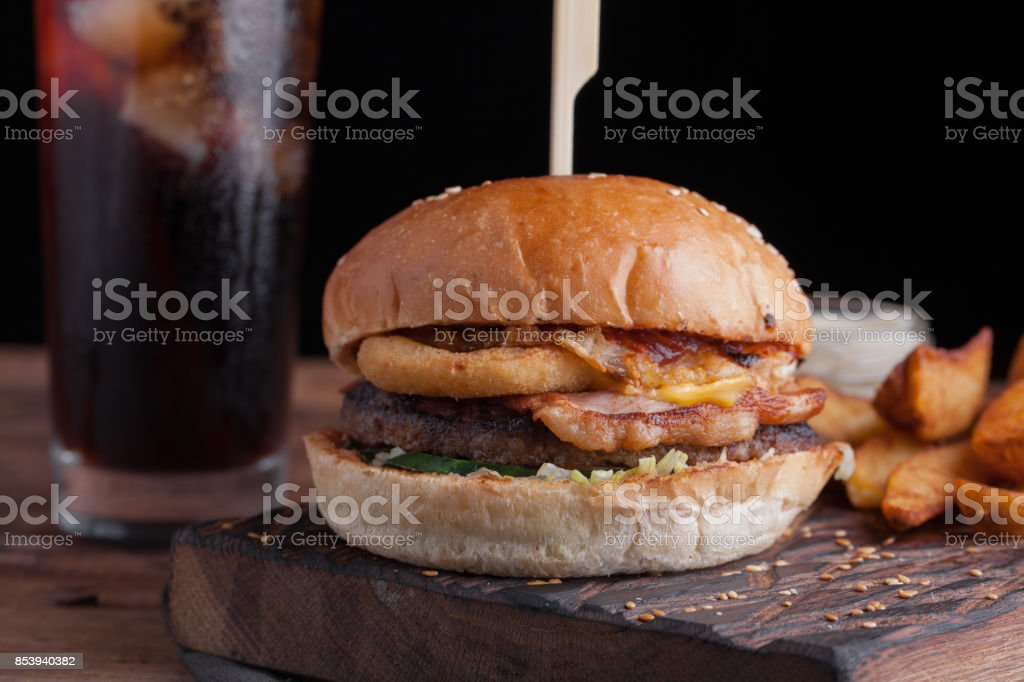 A tasty Burger with snacks in the form of potatoes with white garlic sauce and a glass of cold Cola. juicy Burger with onion rings, bacon and cheese on a dark wood background stock photo