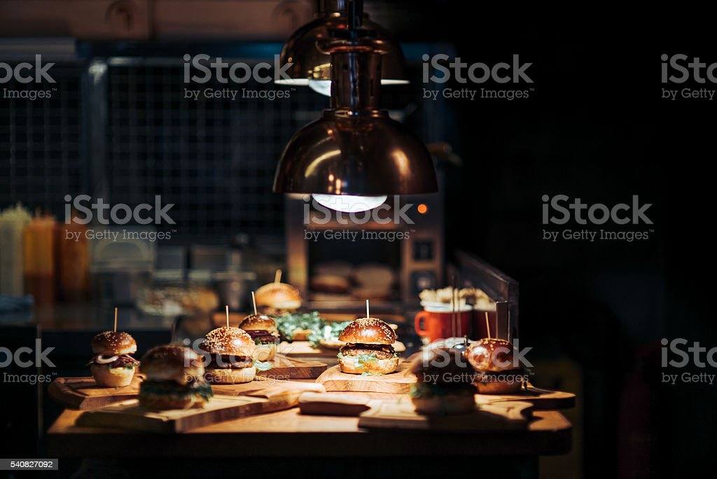 Tasty burgers on wooden trays in bar stock photo