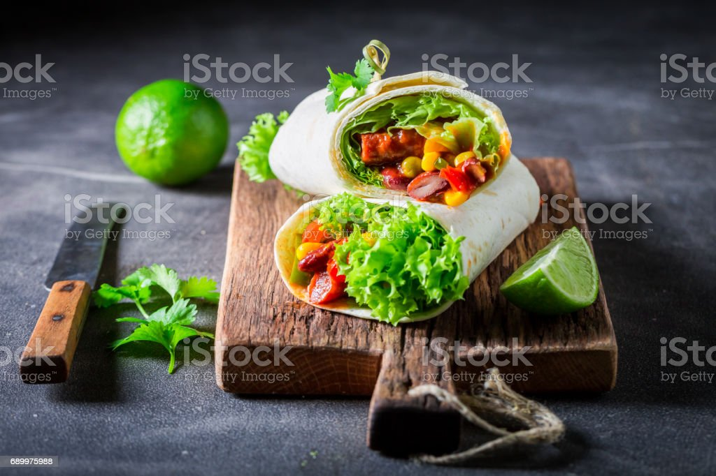 Tasty burrito with tomato sauce, vegetables and meat stock photo
