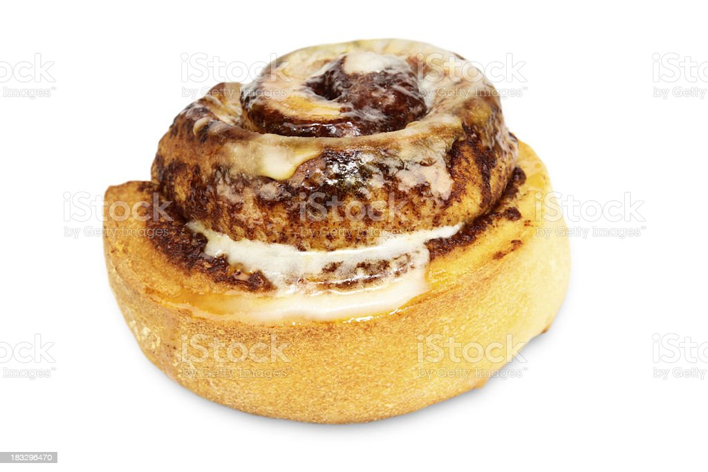 A tasty cinnamon bun with icing on a white background royalty-free stock photo