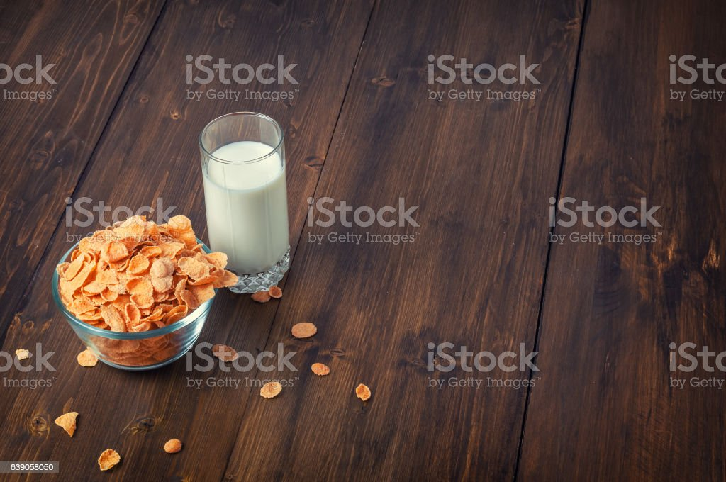 Tasty corn flakes in bowl with glass of milk stock photo