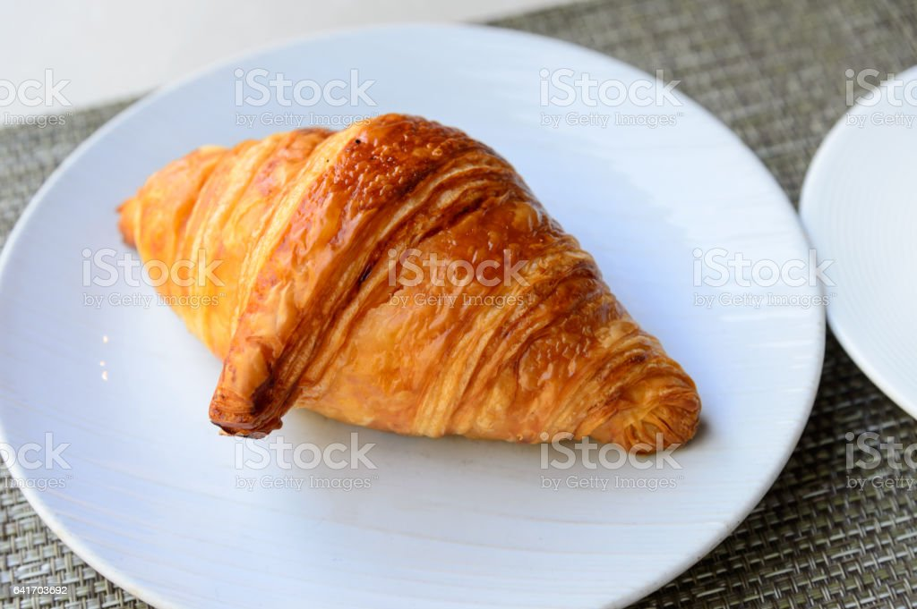 Tasty croissant on the dish stock photo