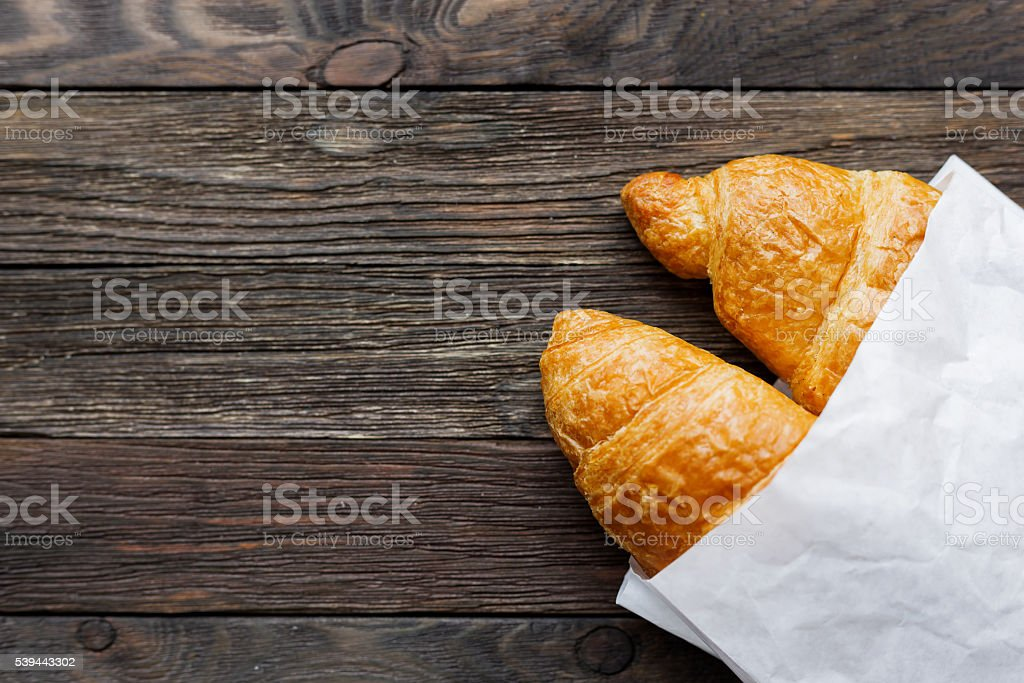 Tasty croissants in white paper bag. Rustic wooden background. stock photo