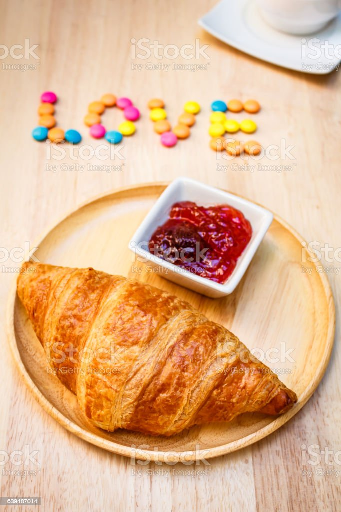 Tasty croissants with jam on wooden background. stock photo