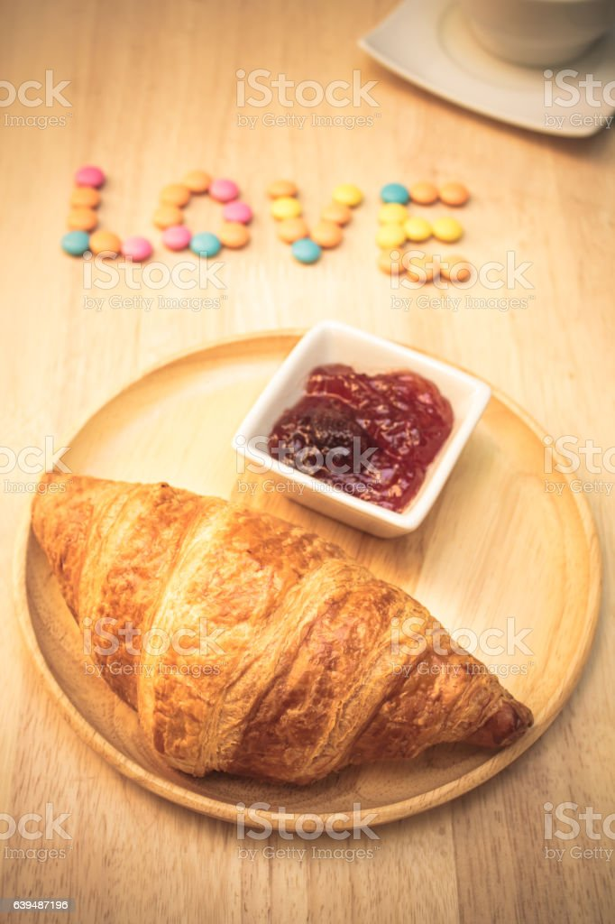 Tasty croissants with jam on wooden background, still life style stock photo