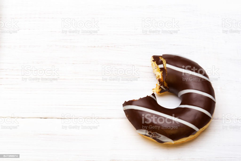 Tasty donuts with icing and chocolate on white wooden background stock photo