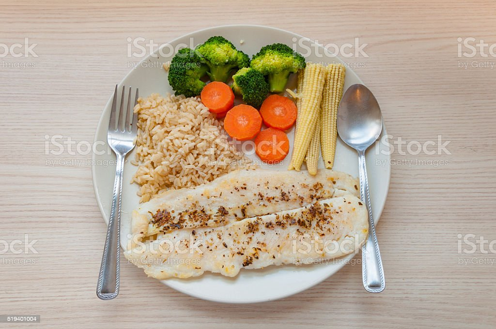Tasty fish fillet steak with steamed vegetables and brown rice. stock photo
