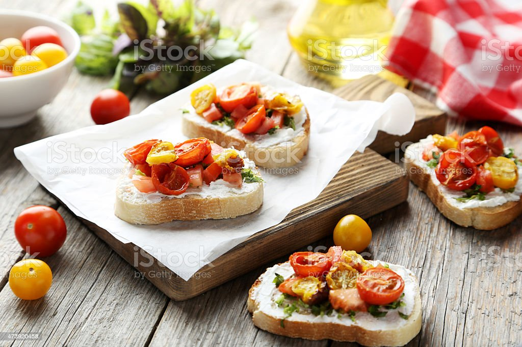 Tasty fresh bruschetta with tomatoes on cutting board stock photo