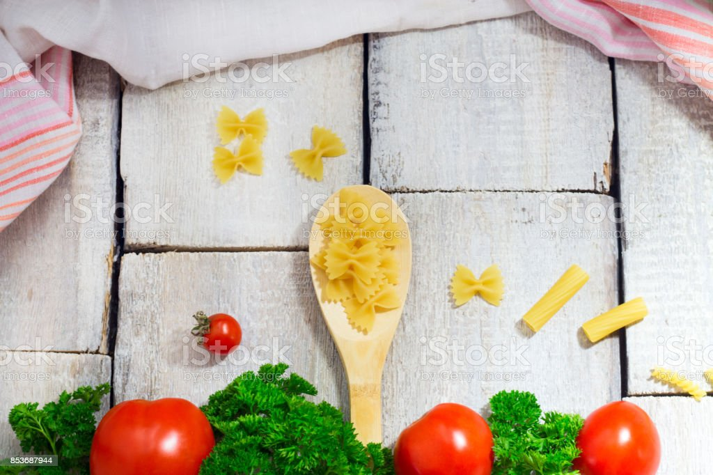 Tasty Fresh Colorful Ingredients for Cooking Pasta Tagliatelle with Fresh Parsley and Tomatoes. Horizontal. Wooden Table Background. stock photo