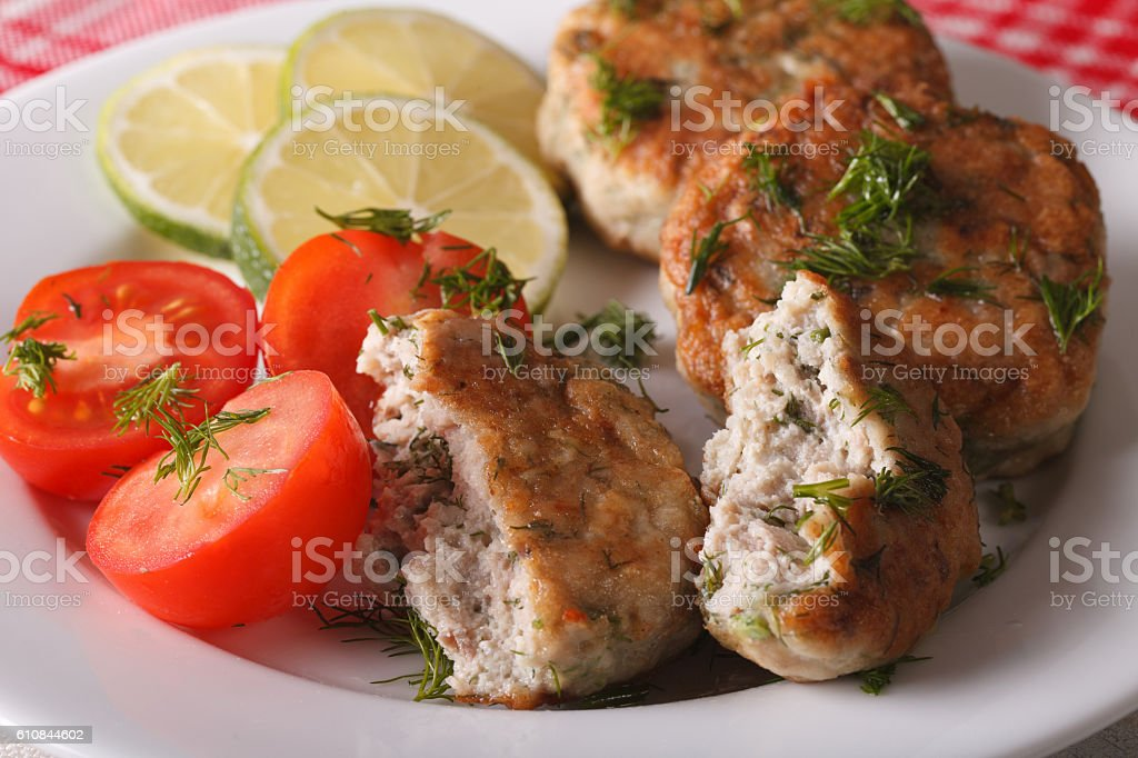 Tasty fried fish cake with herbs close-up on plate. horizontal stock photo