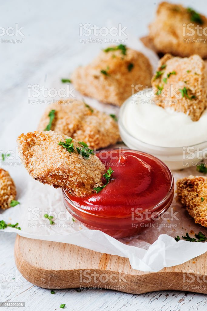 Tasty golden nuggets with red and white sauces stock photo