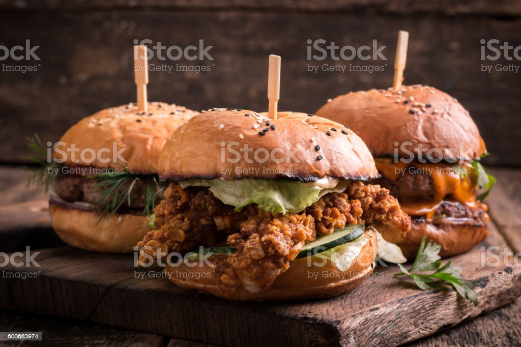 Tasty grilled burger with lettuce and mayonnaise , rustic wooden table stock photo