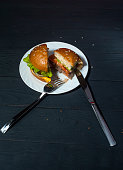 Tasty hamburger on plate with fork and knife