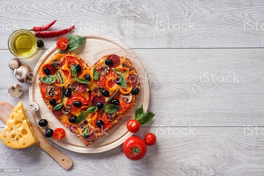Tasty heart shaped pizza decorated with vegetables and herbs stock photo