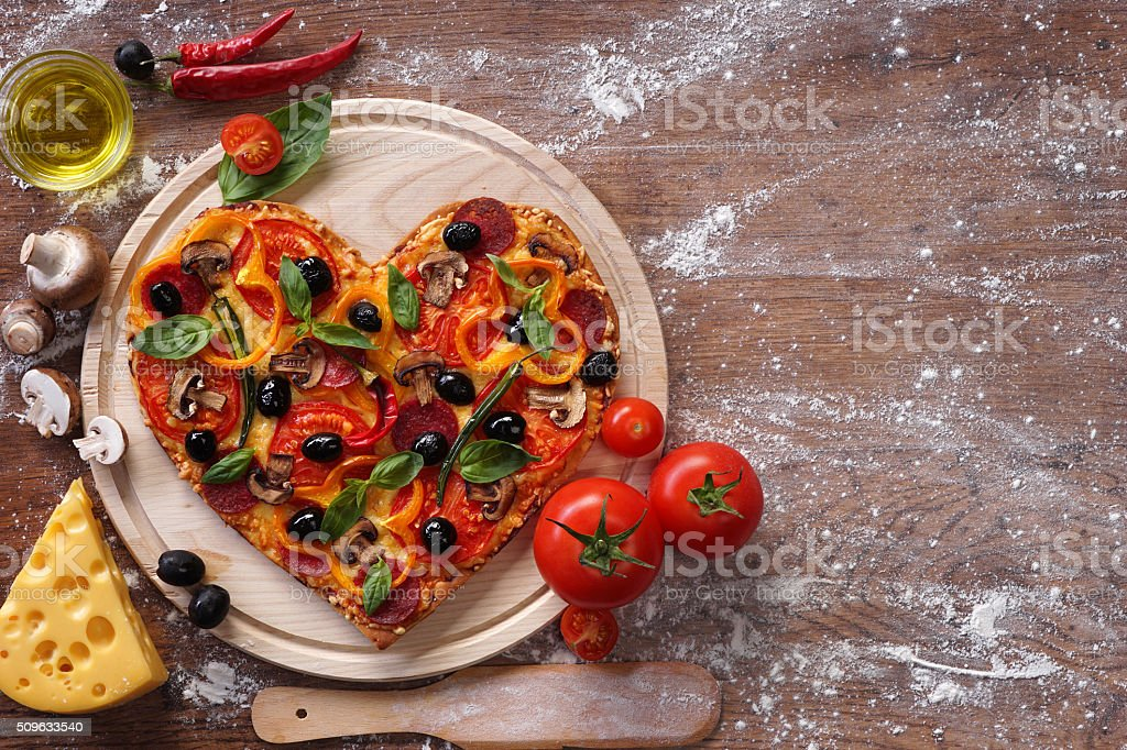 Tasty heart shaped pizza decorated with vegetables stock photo