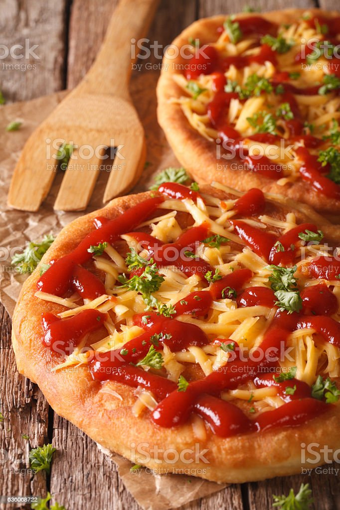 Tasty langos with cheese and ketchup close-up. Vertical stock photo