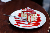 Tasty piece of cheesecake with berry sauce on plate closeup
