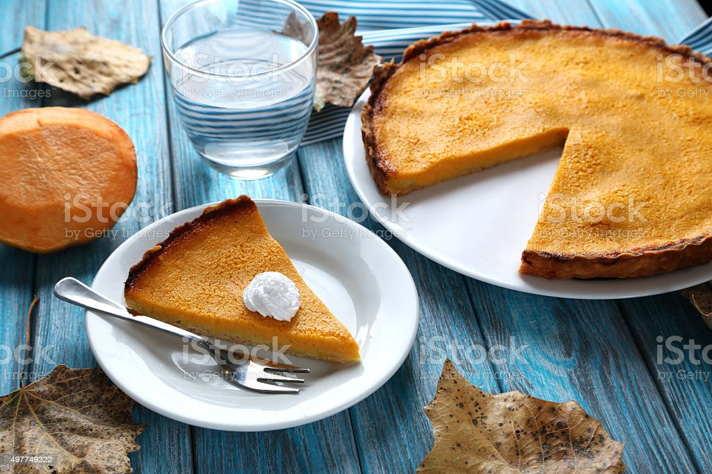 Tasty pumpkin pie on plate on a blue wooden table stock photo