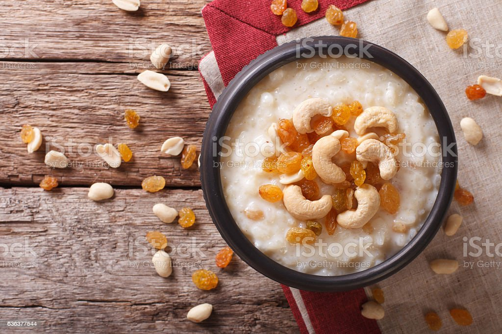 Tasty rice pudding with nuts and raisins close-up. horizontal stock photo