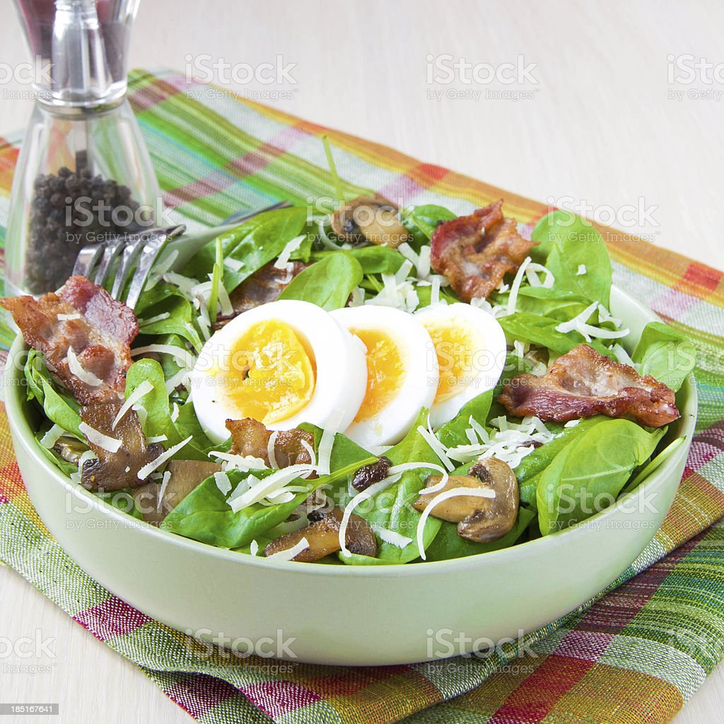 Tasty salad with spinach, bacon, champignon mushrooms, cheese, egg stock photo
