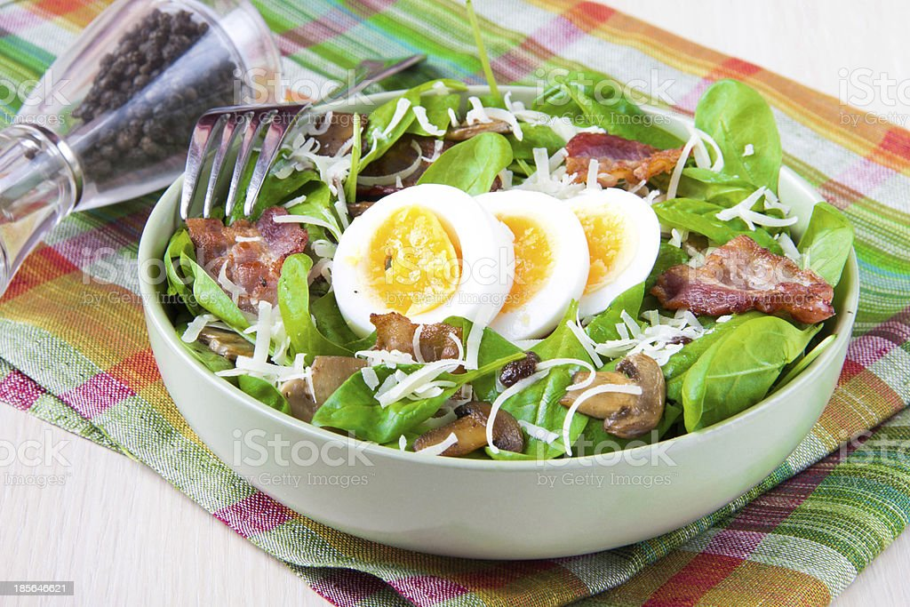 Tasty salad with spinach, bacon, mushrooms, cheese, egg stock photo