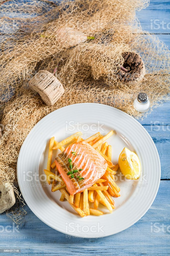 Tasty salmon with chips with lemon on blue table stock photo