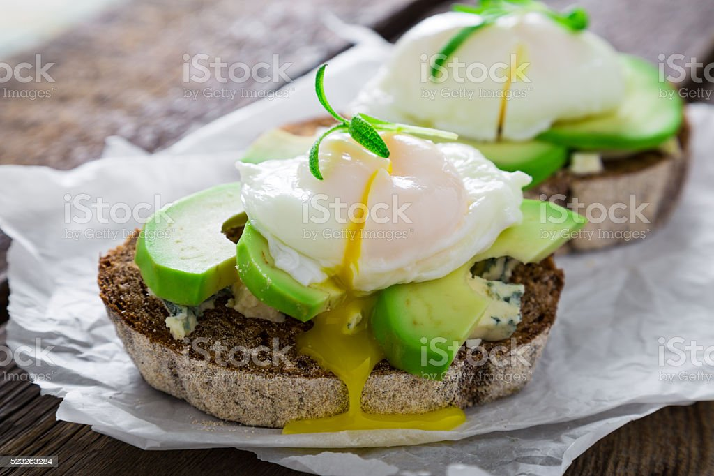 Tasty sandwich with avocado blue cheese and poached egg stock photo
