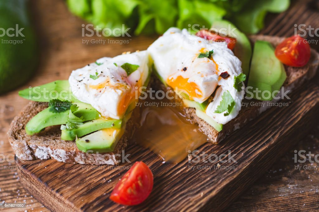 Tasty sandwich with poached egg and avocado stock photo