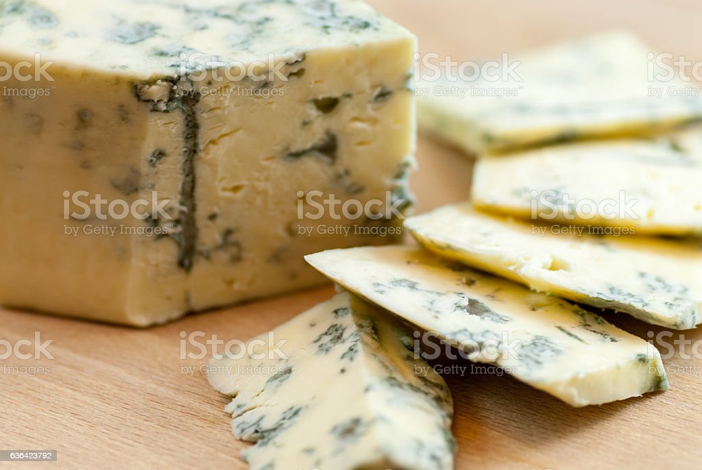 tasty sliced moldy cheese on wooden plate stock photo