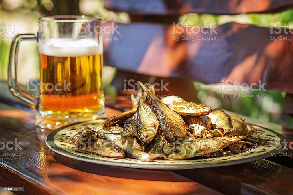 Tasty smoked herring lies on plate with glass of beer stock photo