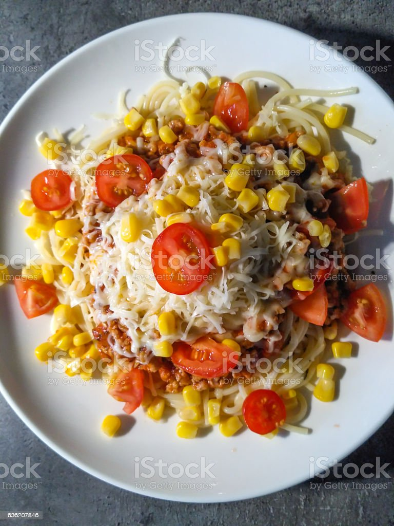 Tasty spaghetti bolognese with sweet corn and tomatoes. stock photo