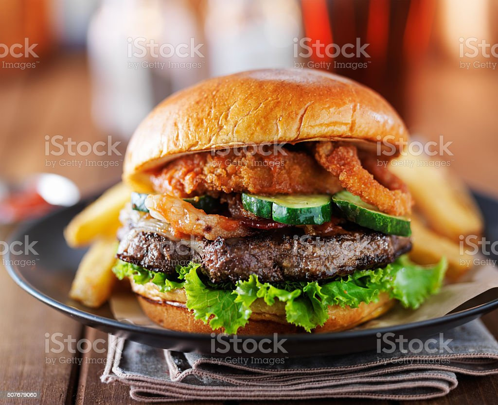 tasty thick cheeseburger with onion rings and pickles stock photo