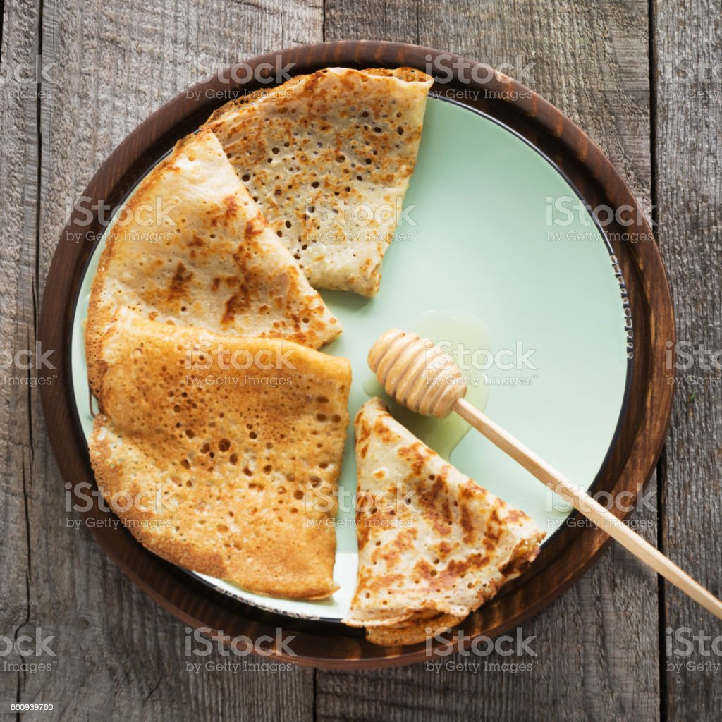 Tasty traditional russian breakfast of pancakes with honey on plate. Rustic style. Space for your text. stock photo